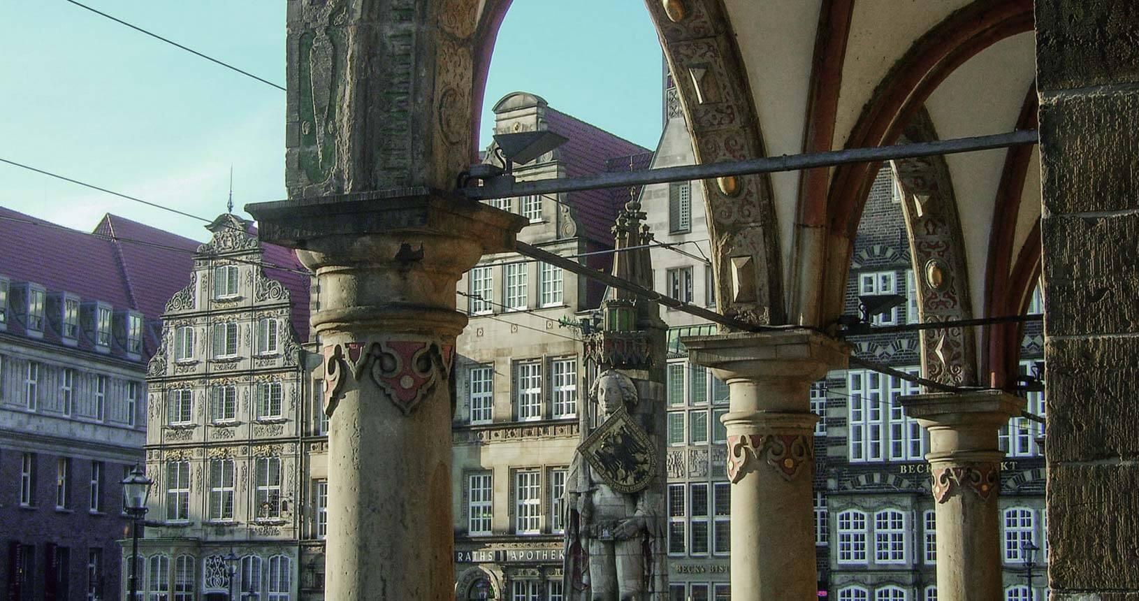 Blick aus den Rathausarkaden auf die Roland-Statue und die wieder aufgebauten historischen Häuser