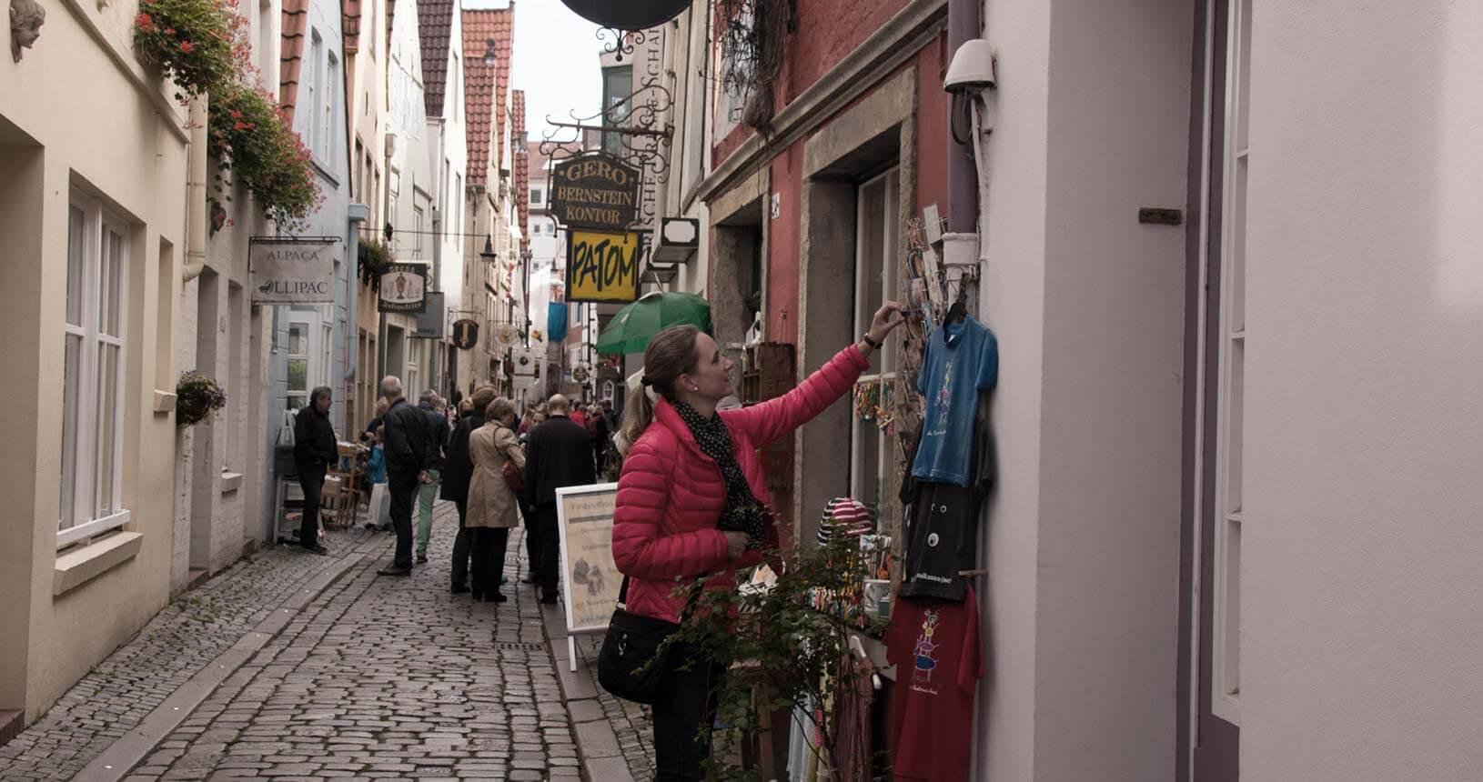 Menschen im Schnoor, im Vordergrund Frau in rosafarbener Jacke, sich Auslage genau anschaut