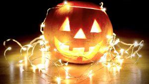 Von innen erleuchteter Halloween-Kürbis mit Fratze und Lichterkette